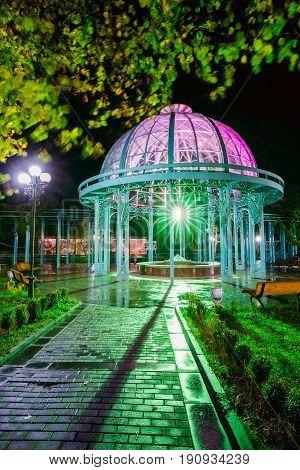 Borjomi, Samtskhe-Javakheti, Georgia. Pavilion Above Hot Spring Of Borjomi Mineral Water. Famous Local Landmark Is City Park At Autumn October Night In Illumination Lights. Long Exposure.