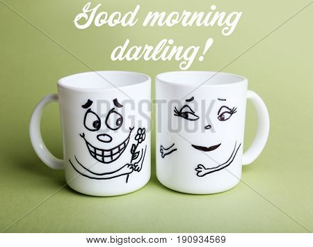 Text GOOD MORNING DARLING and cups with funny faces on color background