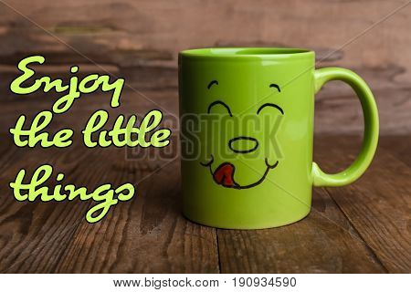 Text ENJOY THE LITTLE THINGS and cup with funny face on wooden background