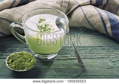 Matcha green tea latte on a wooden background