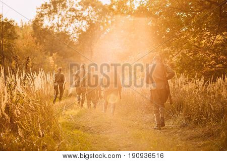 Group Of Reenactors Men Dressed As Russian Soviet Red Army Infantry Soldiers Of World War II Marching In Autumn Forest With Weapons At Sunset Time During Historical Reenactment.