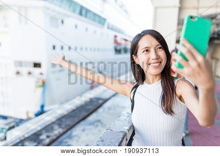 Woman taking selfie with cruise in Hong Kong
