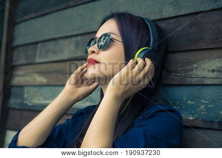 young happy asian woman using headphone to listen to her music selective focus and vintage color tone