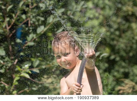 boy squirting water from a hose. A photo