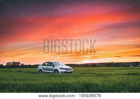 Gomel, Belarus - May 27, 2017: Volkswagen Polo Vento Car Sedan On Country Road In Spring Wheat Field Under Colorful Dramatic Sky At Sunset Or Sunrise Dawn. Concept Of Summer Trip Or Travel On VW Cars.