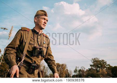 Dyatlovichi, Belarus - October 1, 2016: Reenactor Man Dressed As Russian Soviet Red Army Infantry Soldier Of World War II Walking In Autumn Meadow At Historical Reenactment