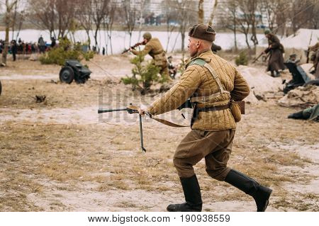 Gomel, Belarus - November 26, 2016: Re-enactor Dressed As Russian Soviet Red Army Soldiers Of World War II Running To Enemy Positions With Machine Gun In Autumn Field During Historical Reenactment.
