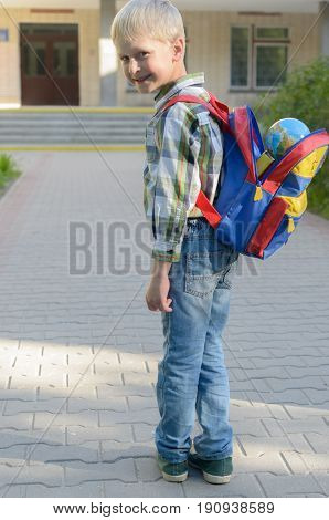 A boy with a knapsack, books and a globe goes to school after a long summer
