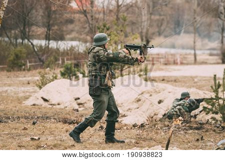 Gomel, Belarus - November 26, 2016: Re-enactor Dressed As German Wehrmacht Infantry Soldier In World War II Open Fire From Sub-machine Gun During Historical Reenactment.