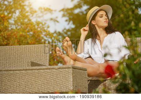Woman resting in summer in her home garden