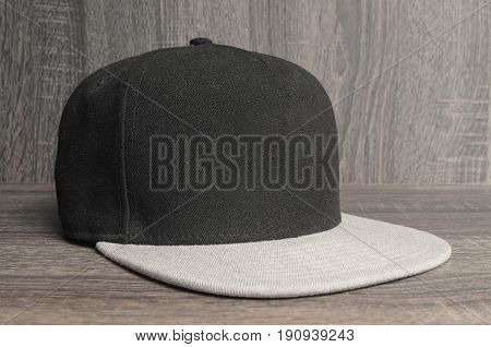 Black Cap With Light Gray Flap On A Wooden Background