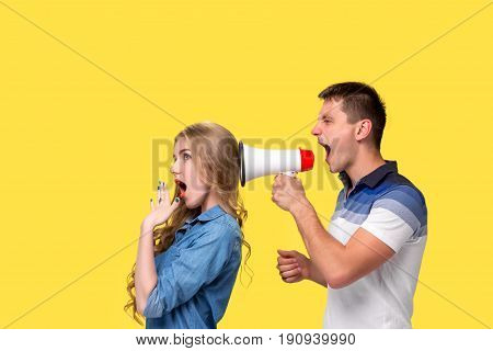 Man shouting in megaphones with woman at each other