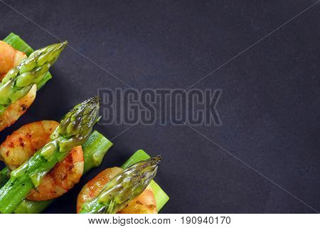 green asparagus with tiger prawn shrimp on a dark gray plate top view from above with large copy space festive appetizer or buffet snack