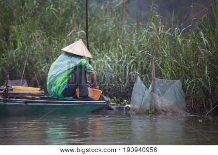 Tam Coc, Ninh Binh, Vietnam - March 16, 2017: Fisher man in a wooden boat on Ngo Dong River at the Tam Coc portion, Ninh Binh Province, Vietnam