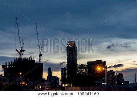 Silhouette construction is high building. structure building background at twilight. Urban life cityscape in Bangkok. Building the new condominium in town.