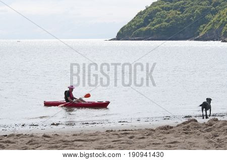 Oxwich beach, Wales, 14-08-2010: An old man sitting in a bright red kayak in Wales.