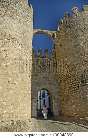 Alentejo, Portugal, 25-September-2007: A woman standing in the gateway of a majestic and ancient castle in Mertola village.