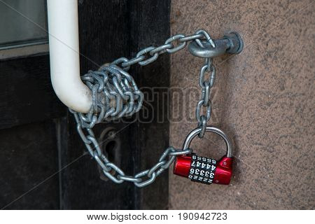Red code lock hanging on the chain closing the front door.