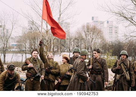 Gomel, Belarus - November 26, 2016: Joyful Girl Young Woman Re-enactor Dressed As Russian Soviet Red Army Soldier Of World War II Waving A Red Flag In Honor Of Victory During Historical Reenactment
