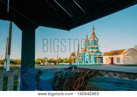 Old Wooden Orthodox Church Of The Nativity Of The Virgin Mary At Sunset In Village Krasnyy Partizan, Dobrush District, Gomel Region, Belarus. View From Old Village Well