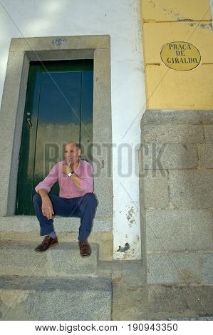 Evora, Alentejo, Portugal, 26-September-2007: A man sitting on the doorstep of a house staring off into the distance in Evora.