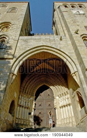 Evora, Alentejo, Portugal, 26-September-2007: A woman standing at the gate of a breathtaking building in Evora.