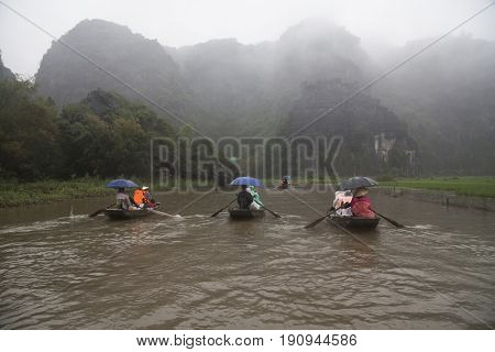 Tam Coc, Ninh Binh, Vietnam - March 16, 2017: Tourists traveling in boat along the Ngo Dong River at the Tam Coc portion, Ninh Binh Province, Vietnam. Rower using her feet to propel oars.