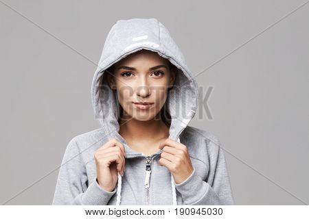 Portrait of brutal sportive girl in hood and sportswear looking at camera over white background. Copy space.