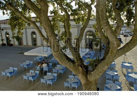 Evora, Alentejo, Portugal, 26-September-2007: Three youngsters sitting at a table on a colourful terrace in Evora.