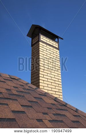 The roof of a house with shingles and chimney