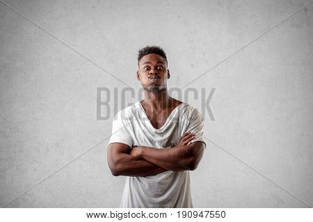Muscular black guy standing with crossed arms