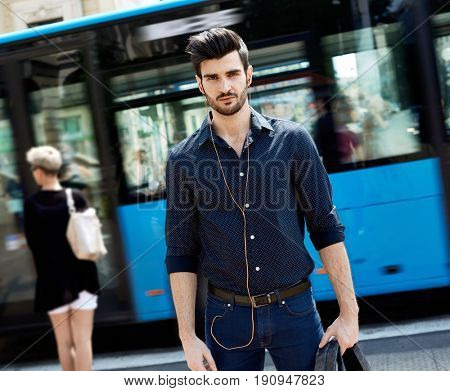 Handsome young man walking in the city, looking at camera.
