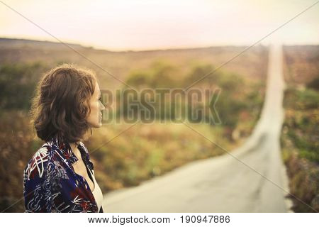 Young woman standing in the countryside looking in the distance towards a long road