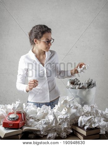 Young secretary surrounded by crushed paper