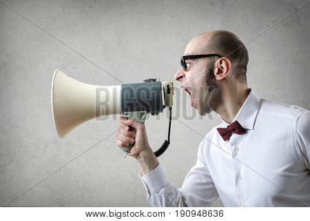 Determined man shouting into a megaphone