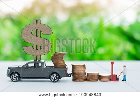 Miniature truck with dollar sign carrying stack of coins worker loading stack of coins using as a business concept.