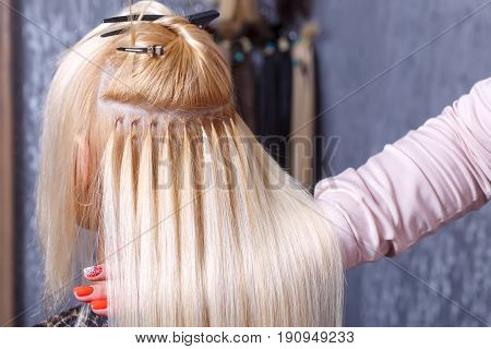 The hairdresser does hair extensions to a young girl, a blonde in a beauty salon. Professional hair care. Selective focus.
