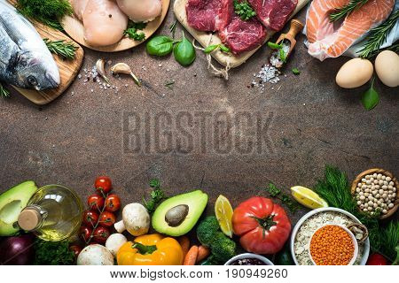 Balanced diet food background. Organic food for healthy nutrition. Meat fish beans and vegetables. Top view copy space on stone table.