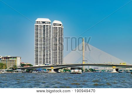 Bangkok, Thailand - December 22, 2015: People travelling by boat in Chao Phraya river overlooking the modern Bangkok with skyscrapers and The Rama VIII bridge Thailand