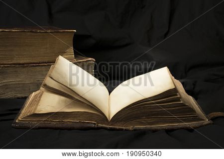 Open Book With Light Spotlight On Text With Books On Background.