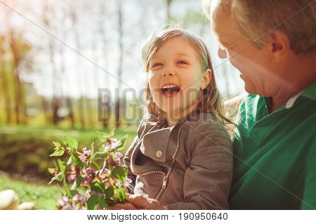 Cute little girl holding flowers and having fun with grandfather in woods together.