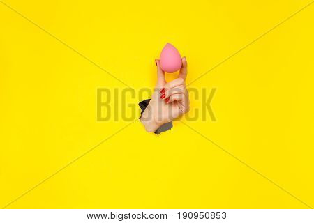 Crop hand of woman with manicure holding pink cosmetic sponge.