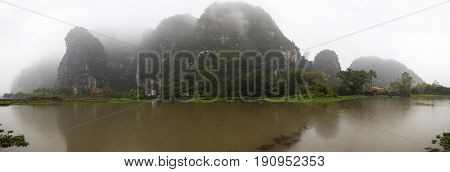 Tam Coc, Ninh Binh, Vietnam - March 1, 2017: Panoramic view of limestone mountains along the Ngo Dong river at Tam Coc, Ninh Binh, Vietnam