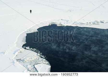 Ice melts on the winter river. Pieces of ice on the water after the passage of an icebreaker. A man walks through the snow. Russia, winter. The Moscow River