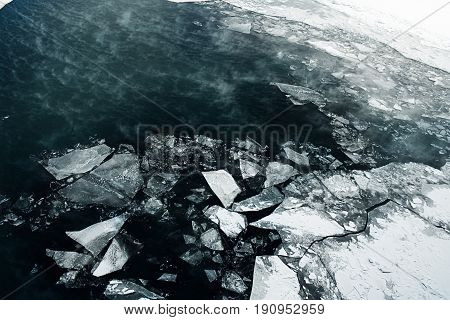 Ice melts on the winter river. Pieces of ice on the water after the passage of an icebreaker.