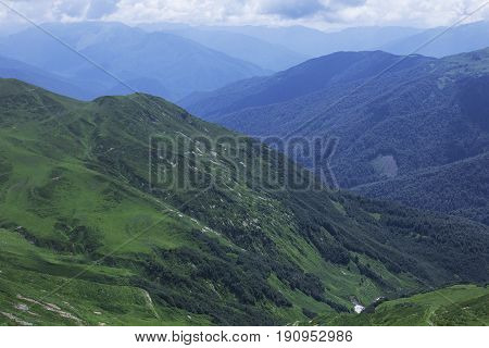 Mountain forests, Alpine meadows and blue sky. Abkhazia. Mountain landscape.