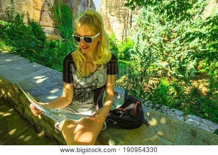 Travel Greece tourist woman on Europe looking at map outdoors. Blond caucasian happy female holding travel map at St. Nicholas Anapafsas Monastery in Meteora, Thessaly, Greece. Tourism people concept.