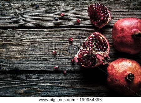 Ripe pomegranates, napkin and table knife on white wooden background a