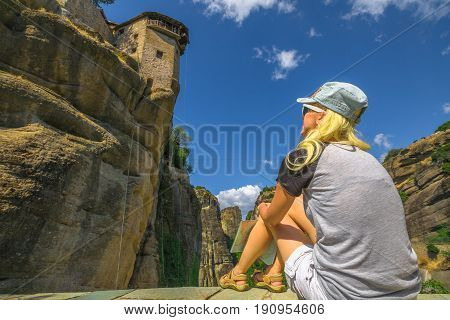 Caucasian beautiful blonde tourist looking up the St. Nicholas Anapafsas Monastery in Meteora, Thessaly, Greece. Tourism and travel in Europe. Woman traveler in landmark and Heritage Site. Bottom view