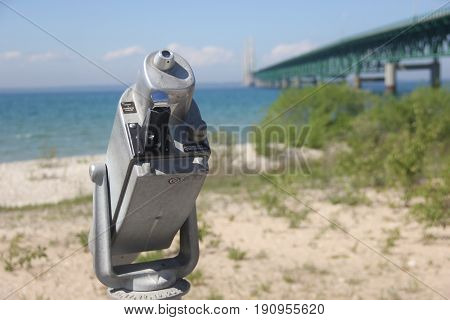 A tower viewer on a beach of Straits of Mackinac, the Mackinac Bridge can be seen in the background